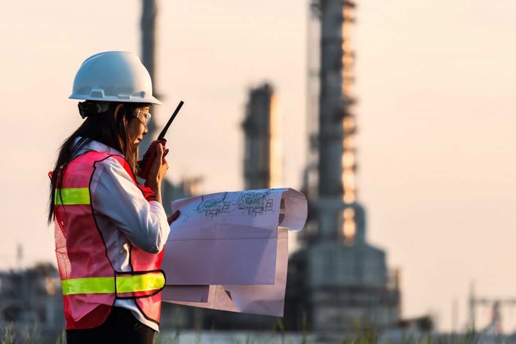 Engineer with blueprints in front of industrial complex